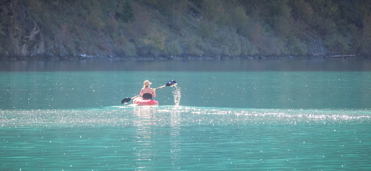 woman canoeing on a blue lake