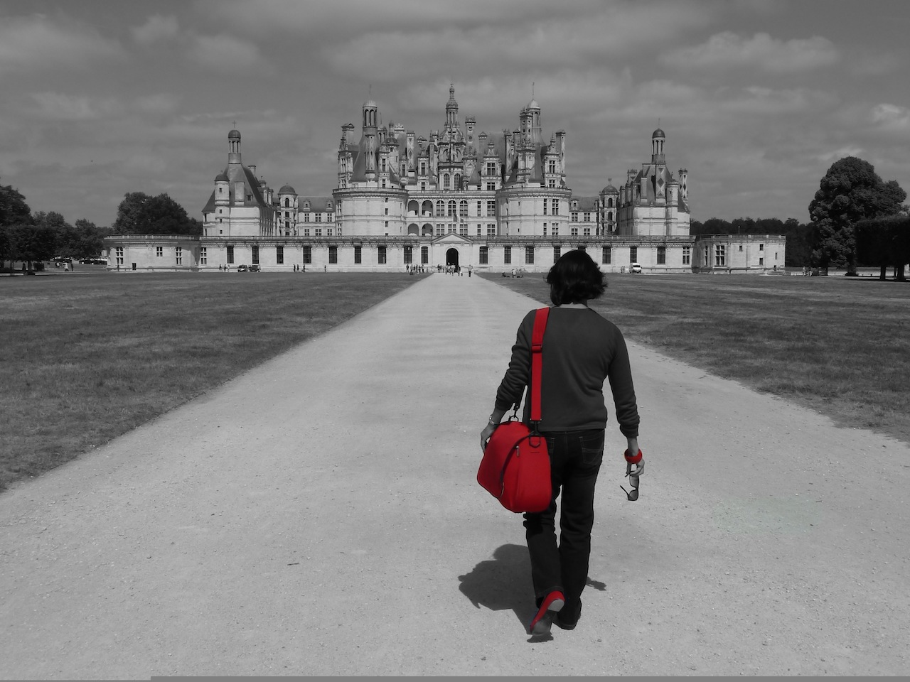 A woman with a red bag and shoes walking toward a very grand chateau in Chambord, France