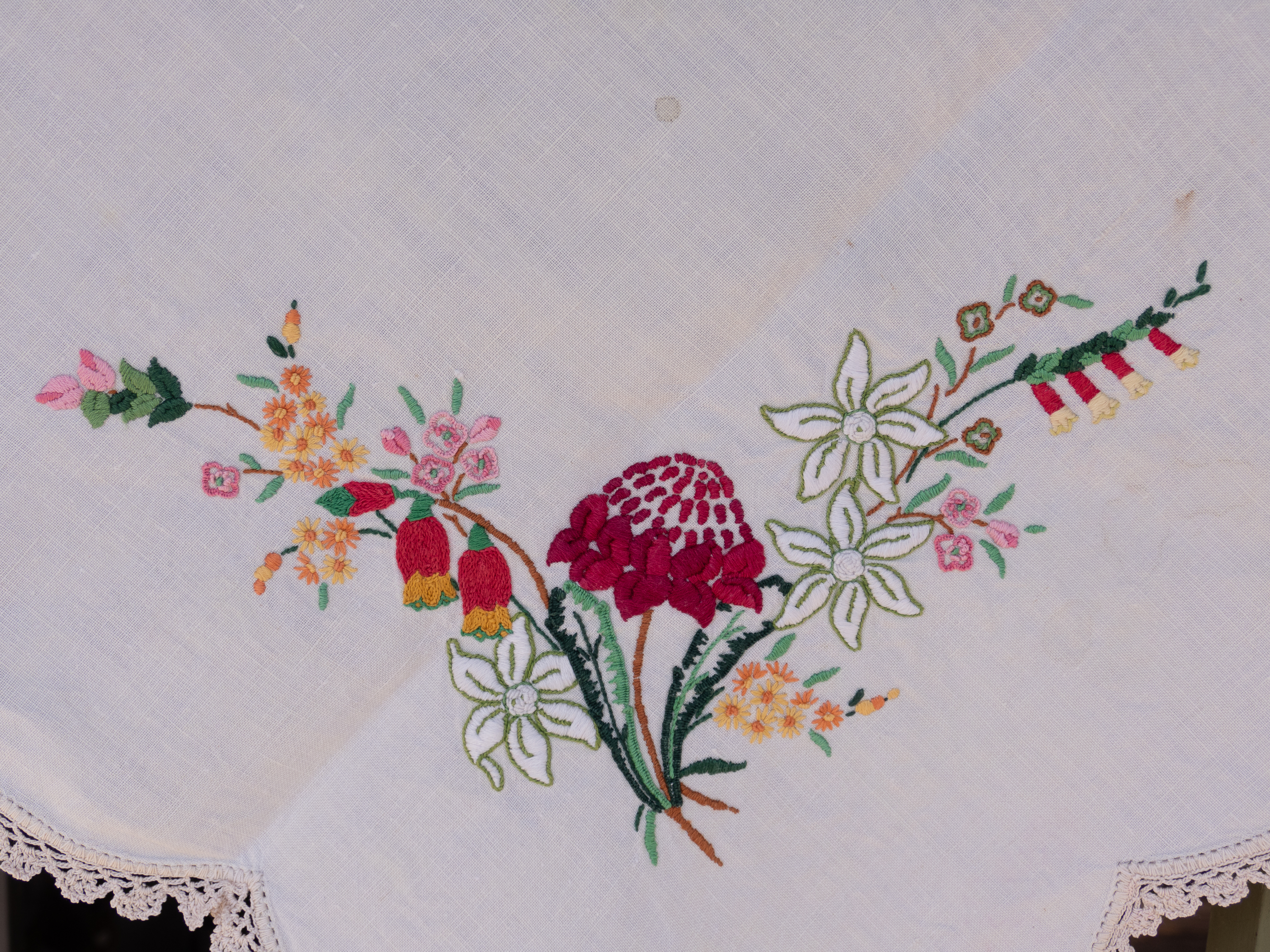 A hand embroidered tablecloth featuring Australian flora