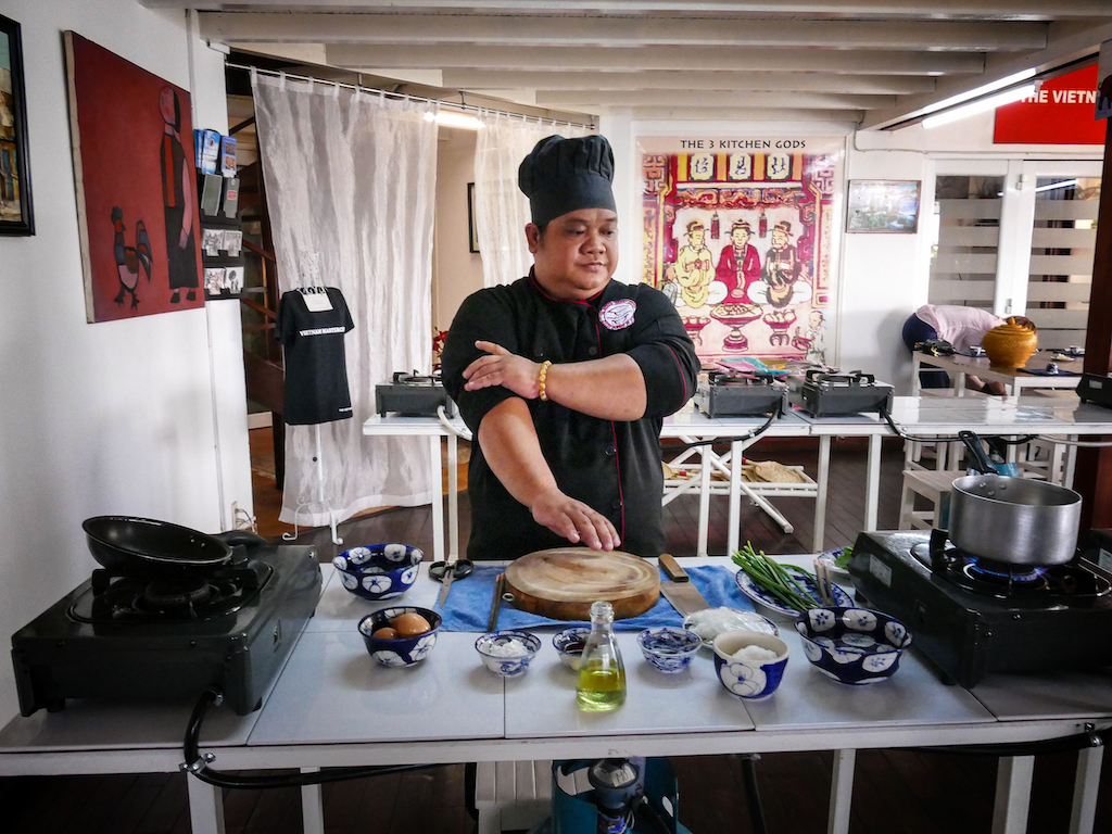 A chef with black hat and jacket rolling up his sleeves preparing to cook