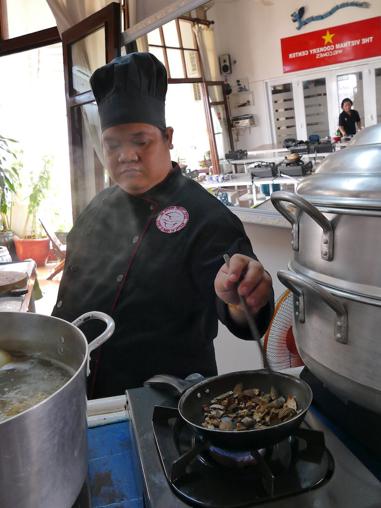 A Chef stiring a pan with various dry spices over a gas flame.