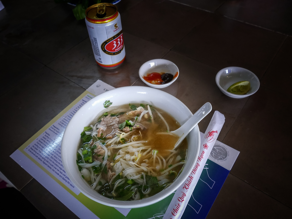 a bowl of beef and noodle soup with a beer on the side