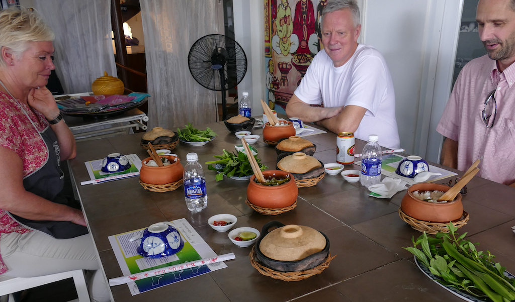 A group of 3 people two men and a women at a table waiting to start eating.