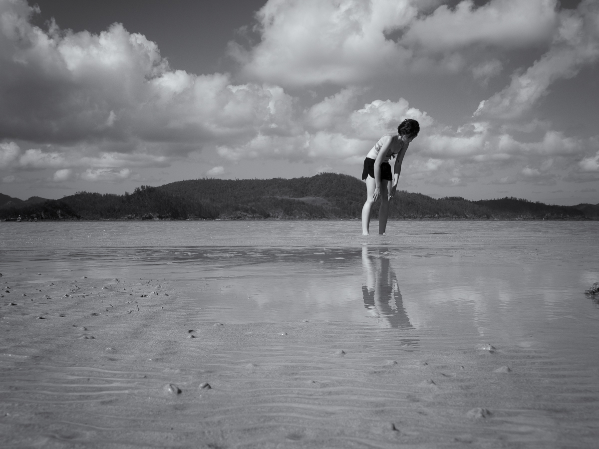 A woman standing in ankle deep water looking for sheels