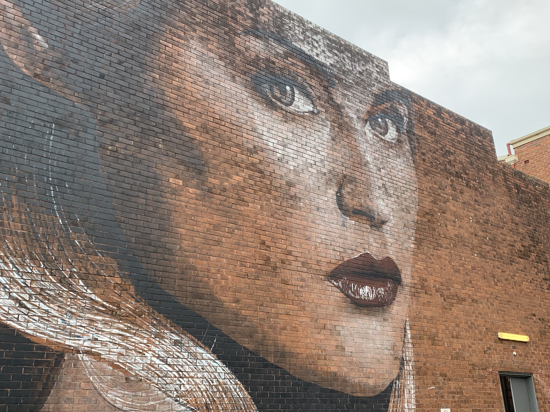 Street mural of a woman with red lips