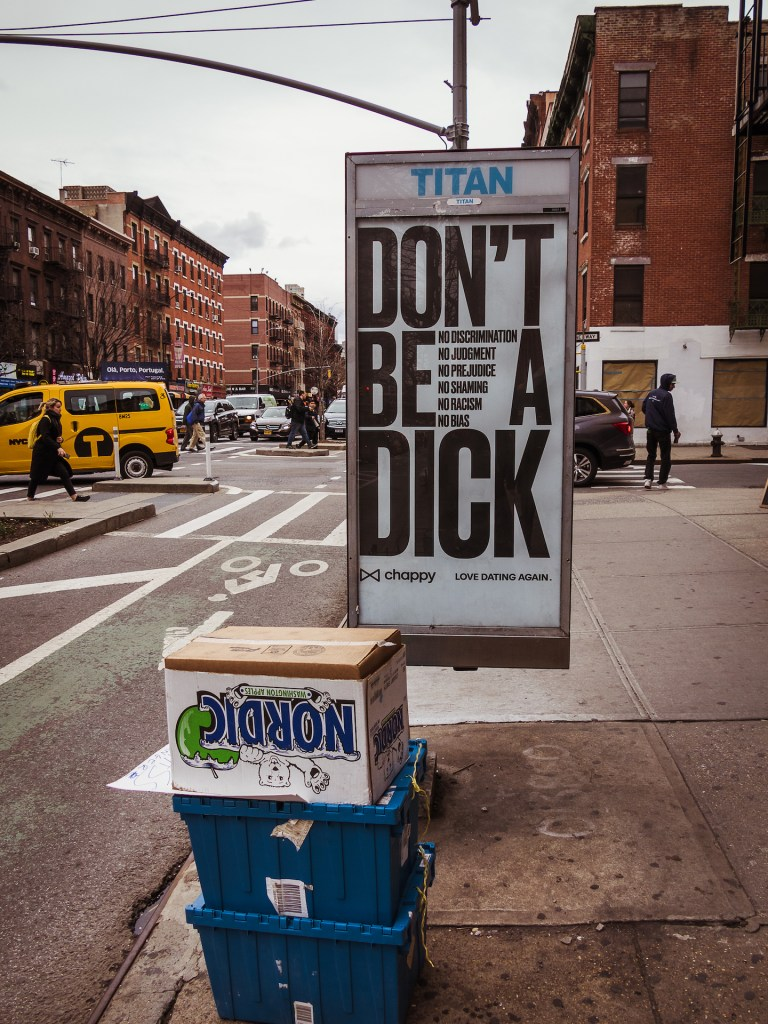 Street scene from New York with a bus sign saying don't be a dick,